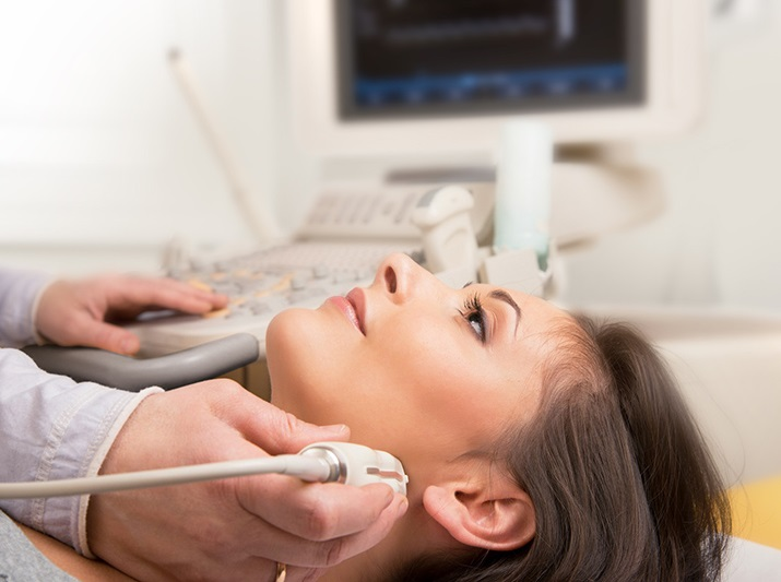 young-woman-doing-neck-ultrasound-examination-at-hospital